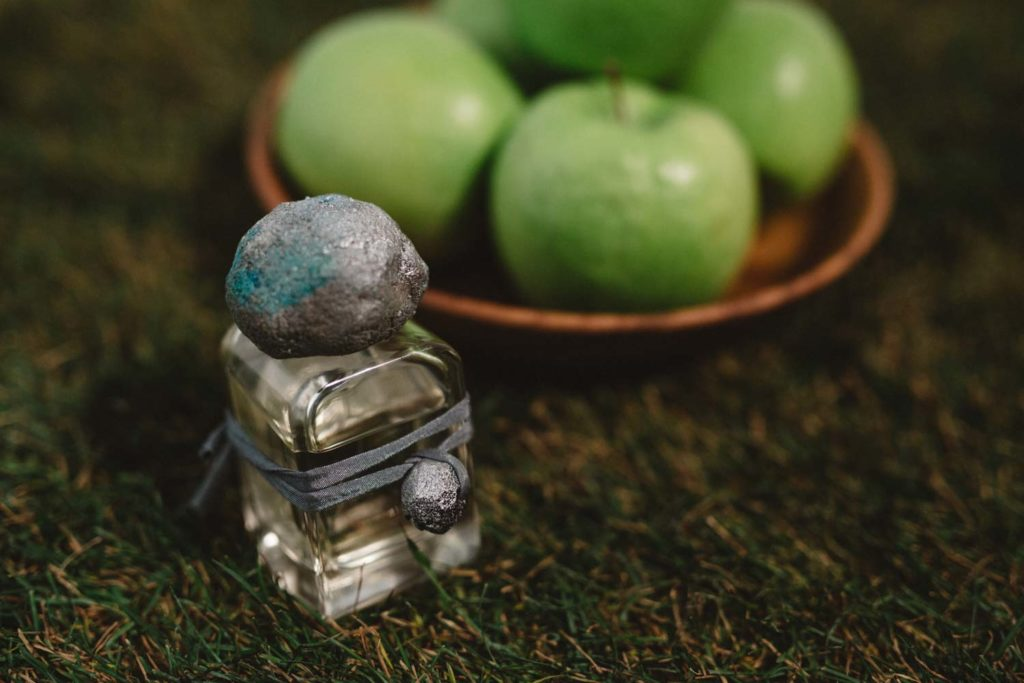 Sirio Extrait de Parfum flacon in glass bottle and hand sculpted cap and charm and green apples on the grass